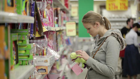 Young woman is choosing toys for her kid. Middle shot with shoppers in background Footage