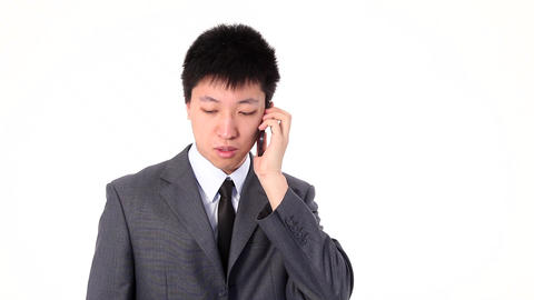 Asian young businessman talking ernestly on a smart phone Footage