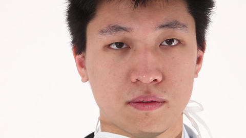 Worried Asian young doctor pulls on protective clothing Stock Video Footage
