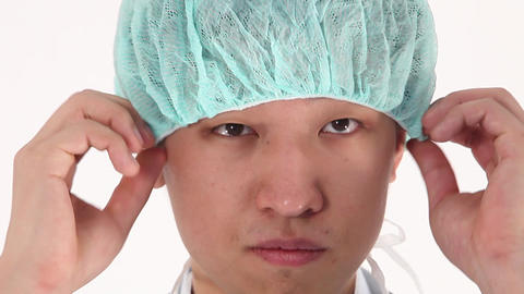 Worried Asian young doctor pulls on protective clothing Footage