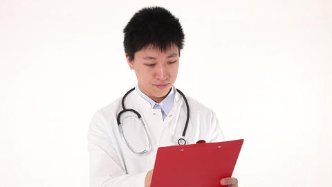 Young Asian Doctor Writing On His Clipboard stock footage