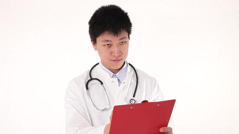 Young asian doctor writing on his clipboard Stock Video Footage
