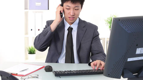 Young Asian businessman working at his desk Stock Video Footage