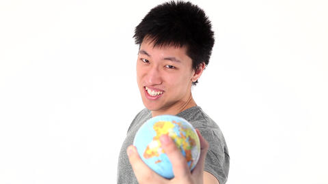 Young Asian man holding globe at camera Footage