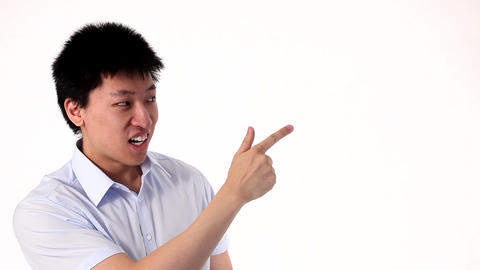 Funny Asian Man Pointing On A White Copy Space stock footage