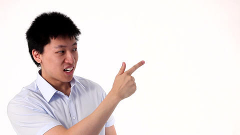 Funny Asian man pointing on a white copy space Stock Video Footage