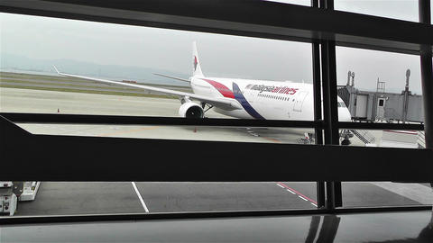 Looking through Window Frames to Malaysia Airline Plane Stock Video Footage
