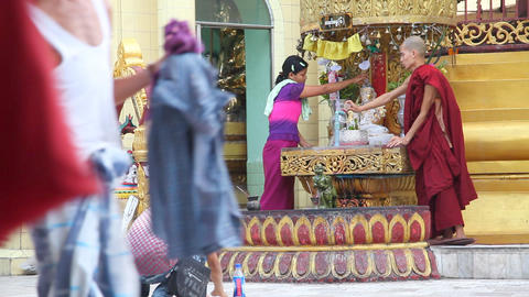 Monk pours water to buddha statue in Sule Pagoda Stock Video Footage
