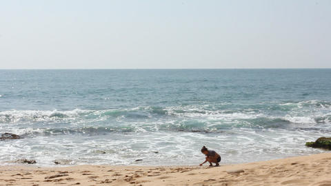Young girl at beach gathering rocks Stock Video Footage