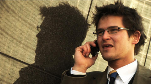 Businessman on mobile in city with reflection Stock Video Footage