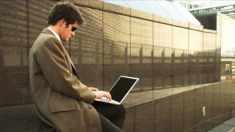 Businessman on laptop in city Stock Video Footage