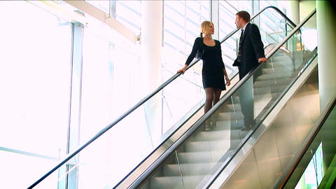 Business couple meeting on moving escalator Footage