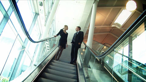 Business couple meeting on moving escalator Stock Video Footage