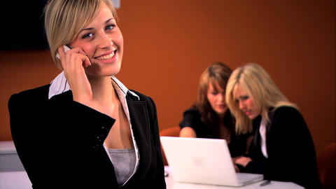 Beautiful blonde businesswoman chats on the cell with her colleagues in background Footage