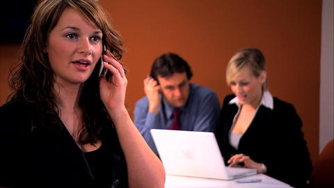 Beautiful businesswoman chats on the cell with her colleagues in background Footage