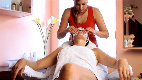 Beautiful brunette girl having facial massage at the... Stock Video Footage