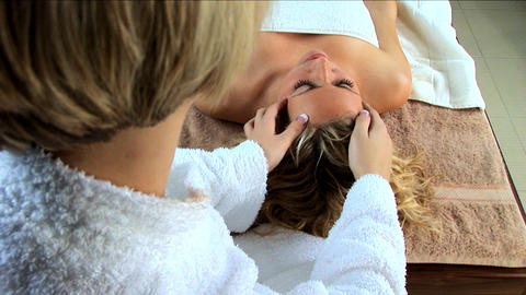 Beautiful blonde girl having facial massage at a health & beauty spa Footage