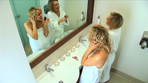Beautiful blonde girls applying cosmetics after treatment... Stock Video Footage