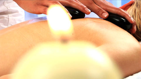 Blonde girl has hot stone massage with candles burning in the foreground Footage