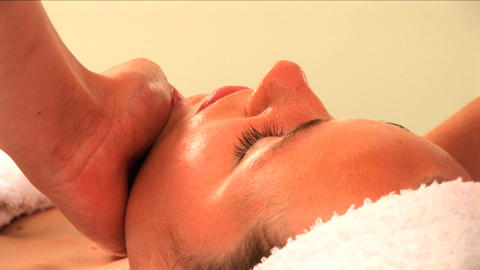 Beautiful blonde girl having facial massage at a health & beauty spa in close-up Footage