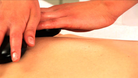 Hands applying hot stone massage in close-up Stock Video Footage