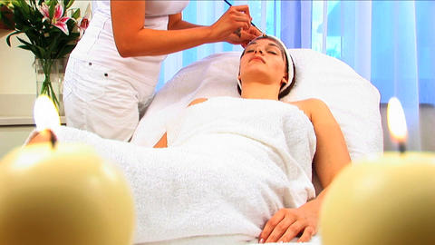 Young brunette girl having facial skin mask applied at beauty spa with candles in foreground Footage
