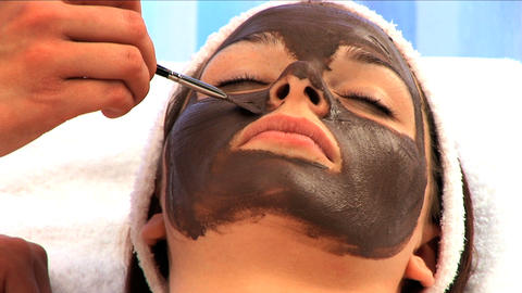 Young brunette girl having facial skin mask applied at health & beauty spa in close-up 影片素材