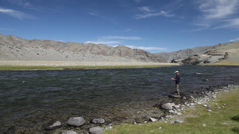 Fisherman with spinning catching fish in Khovd river Stock Video Footage