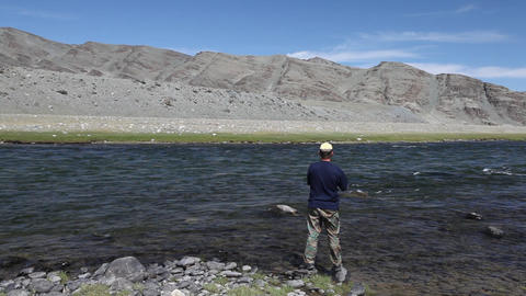 Fisherman with spinning catching fish in Khovd river Footage