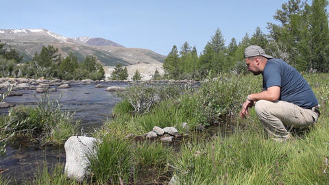 Hiker drink water from mountain river in Mongolian Altai Stock Video Footage