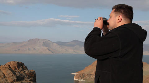Hiker in mountain look into binoculars Stock Video Footage