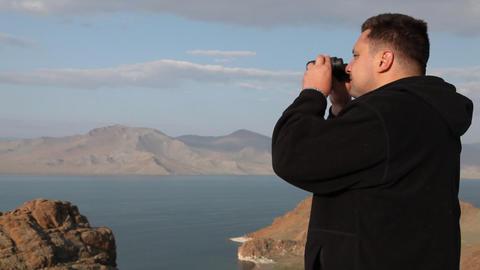 Hiker in mountain look into binoculars Stock Video Footage