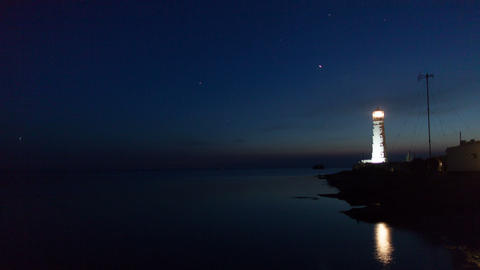 Lighthouse on the water edge near sea at night, timelapse Stock Video Footage