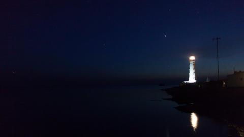 Lighthouse on the water edge near sea at night, timelapse Archivo