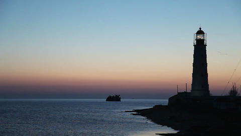 Lighthouse on the water edge near sea at sunset, timelapse Stock Video Footage