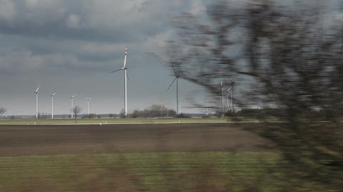 Country landscape view with windmills from moving train,... Stock Video Footage