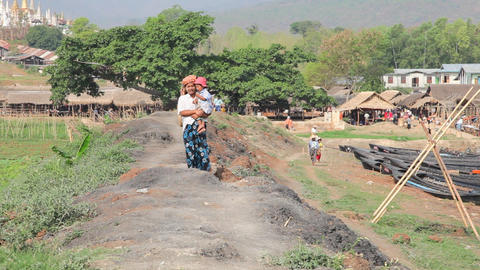 Woman walk near the Taung Tho Market Stock Video Footage