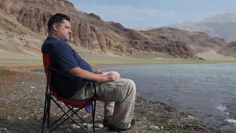 Man relaxing at mountain lake Stock Video Footage