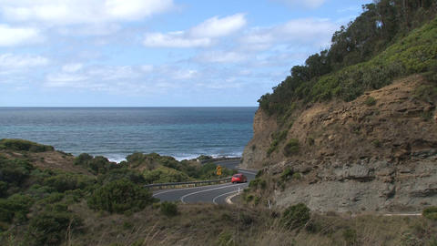 Red car drives down Great Ocean Road Stock Video Footage
