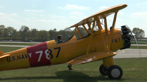 Historic military biplane boeing stearman turning on grass Footage