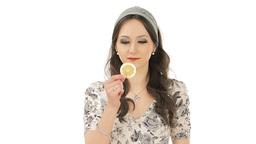 Young brunette tasting a slice of sour lemon Footage