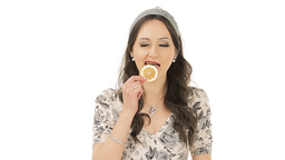 Young brunette tasting a slice of sour lemon Stock Video Footage