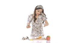 Young brunette chopping apples while speaking on phone Stock Video Footage