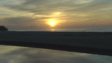 Stunning view of the sun rising in the beach and reflecting over the river, time lapse Footage