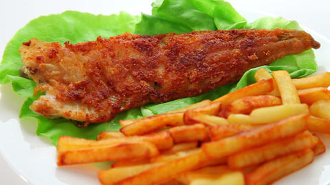 Fried fish dish - fish fillet on green salad with chips Footage