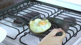 Fried Egg In A Pan. Cooker Takes Out The Egg From The Pan And Serve It On A Plate stock footage