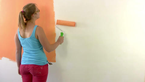 Girl teenager paints a wall in orange Stock Video Footage
