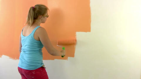 Girl teenager paints a wall in orange Footage