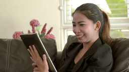 Young Asian Woman Video Chatting with a Friend on Her Tablet Footage