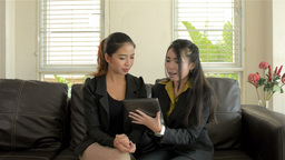 Young Asian Businesswomen Discussing Work on a Tablet... Stock Video Footage